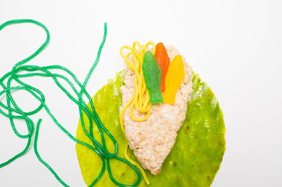 手卷  製作手卷,首先將水果軟糖卷平舖。放上大量的美式沙琪瑪,上頭抹些棉花糖醬,避免放上小魚軟糖和條形橡皮糖時掉落。