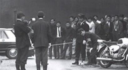 4天後的(12月10日)早上9點30分左右,一輛日產運鈔車裝著2億9430萬7500日元,由日本信託銀行國分寺支行出發,前往東京芝浦電氣(現在的東芝)府中工廠。這些錢是4523名工人的年終獎金,被分別裝在三個保險提箱中。  當運鈔車經過府中監獄後面的府中市榮町學苑路時,被一名騎摩托車的男「警察」攔下。運鈔車司機打開車窗問發生了什麼情況,男「警察」回答「你們銀行巢鴨分行行長的家,被人放了炸彈,剛接到通知你們這輛車也有問題,要檢查一下」。  運鈔車上的人都知道4天前的恐嚇信事件於是都下了車。男子爬上運鈔車後引燃藏在身上的煙霧彈,大叫「要爆炸了,快逃啊」,然後駕駛運鈔車在眾目睽睽之下揚長而去。正當銀行職員們讚嘆「警察」果敢舉動的時候,突然發現「警察」留在現場的摩托車不大對勁,這才知道受騙上當了!