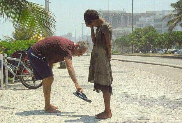 一個男子把鞋子脫下來,給一個赤腳在路上走著的女子