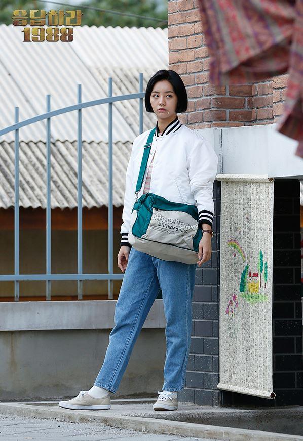 女主角成德善的棒球外套及寬版高腰牛仔褲,再配上超大側背包,不只服裝復古,那頭短髮也非常到位