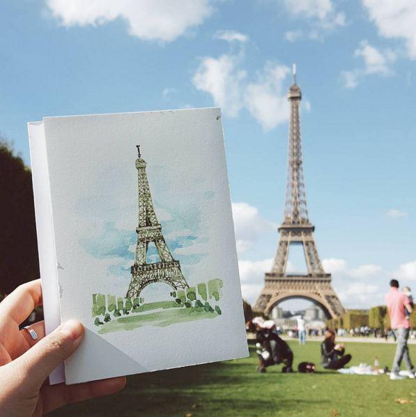 即使是旅行,插畫師也不忘每天作畫分享... 坐在艾菲爾鐵塔前草坪上作畫的插畫師...