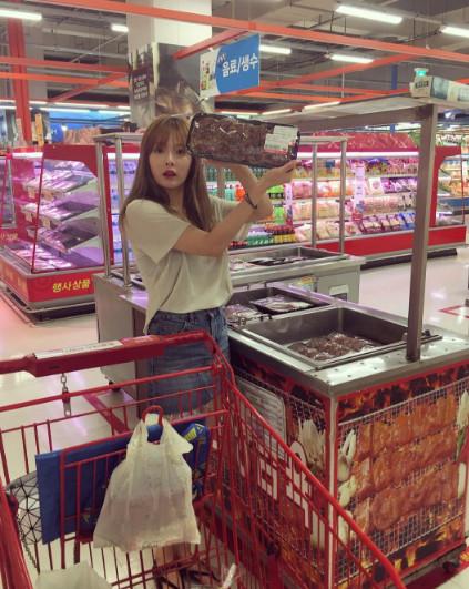 泫雅還在打折區,拿起一大盤打折牛肉,表現的很驚奇的樣子,一副「媽媽,你看韓牛打折哎,買給我 」的可愛模樣。