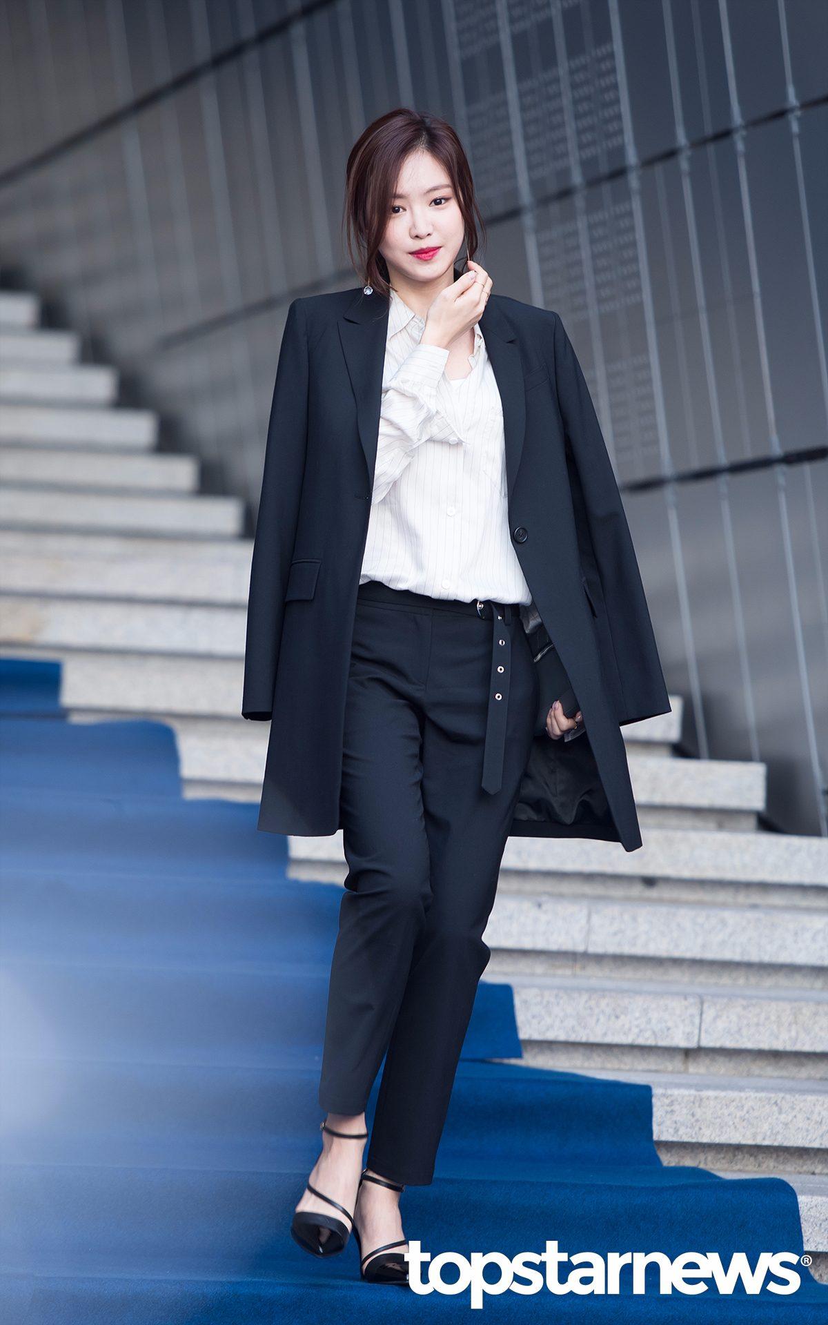 Apink孫娜恩走的是中性風...白色條紋襯衫搭配黑色休閒西褲+綁帶高跟鞋..肩上隨意披著一件黑色大衣,給人簡潔幹練的感覺,非常帥!!