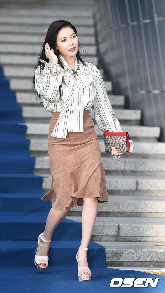 泫雅選用一件象牙白的條紋襯衫搭配包臀荷葉邊過膝裙, 超有女人味...紅色邊手包和白色高跟涼鞋,整體裝扮盡顯高級感...這樣的裝扮非常適合上班族穿,正式中透著成熟女生的柔美風情~