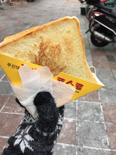 #釜山大學名物吐司명물토스트 在釜山大學商圈中,因多數消費者都是大學生,所以這裡的美食可是走平價路線~而位在釜山大學校園外的名物吐司,在釜山大學生的心中也是不可或缺的早餐美食啊~  土司烤的恰當好處,裡面的餡料更是一點也不馬虎,三層裡可都是塞得滿滿啊!有火腿、起司、蛋、苜蓿芽,酸黃瓜,加上特製的醬料,吃一次後你就會忘不了的好味道!如果不知道該怎麼點餐了話,只要跟店家講「special」就好。