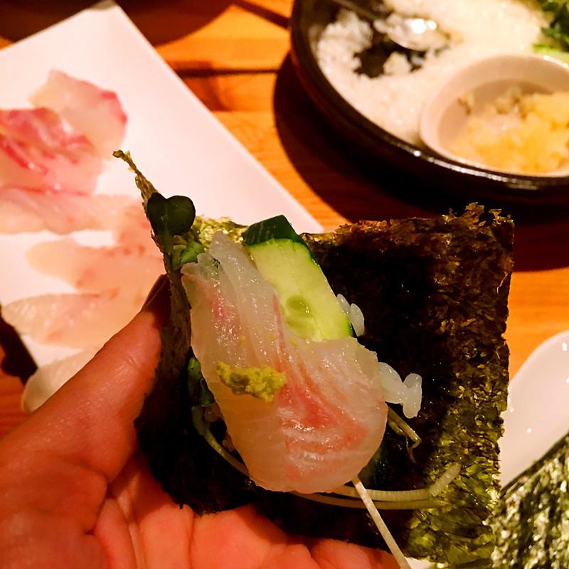 取一片紫菜,依次放上米飯,蔬菜,魚片,再點上醬油和芥末。一口吞下,和單獨吃生魚比起來更加清爽,非常美味!