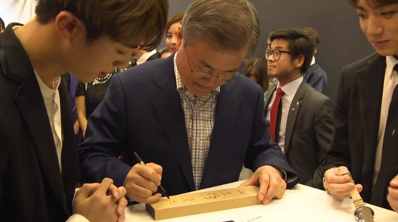 後來JIN還請文在寅總統在先前在參加聯合國送給他們的「文在寅總統手錶」盒子上簽名,在一旁的柾國就把本來戴在手上的手錶拿下來,在旁邊等著要一起簽名ㅋㅋㅋ