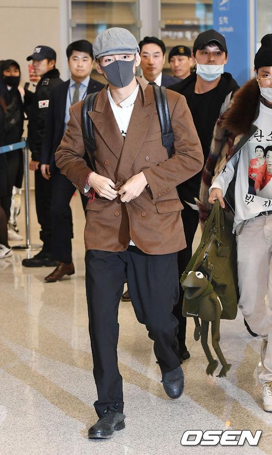 本來穿搭就很有自己風格的V,這次的機場穿搭利用老爺爺風格為主,利用一件咖啡色的西裝外套配上寬鬆的西裝褲,看起來不會有套裝的嚴肅感,反而多了一點街頭風格。